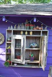 Another curio-filled cabinet attached to a shed wall.