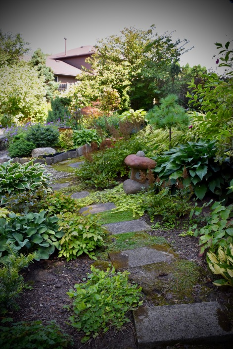Inviting paths through the garden are made of different materials, here in flafstone.