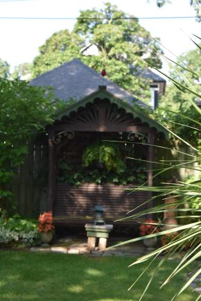 This popuar garden on Garden Walk Buffalo has this sheltered bench in a style that matches thier garden shed.