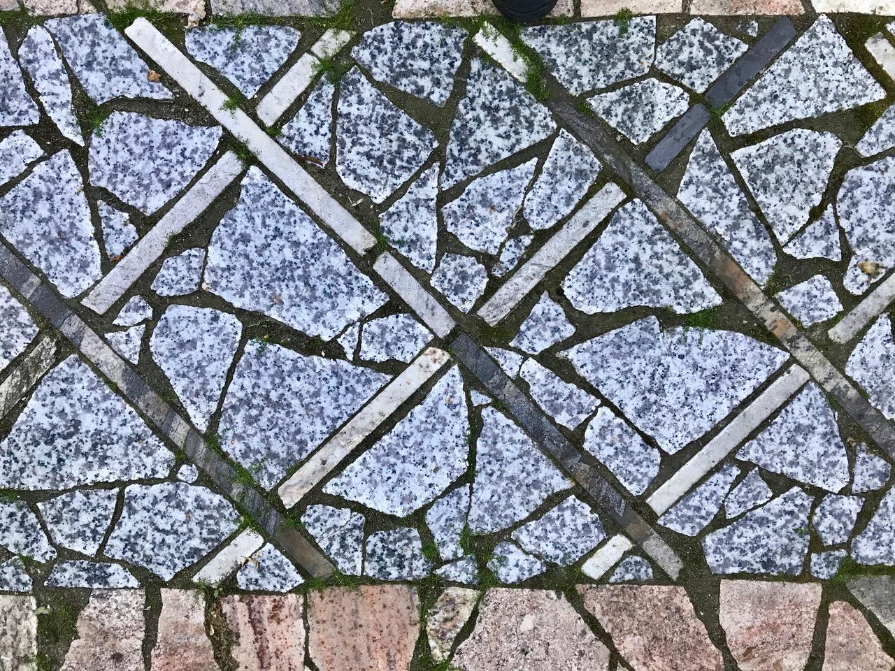 "A scrap marble and granite inlaid ""carpet"" inside a brick patio"
